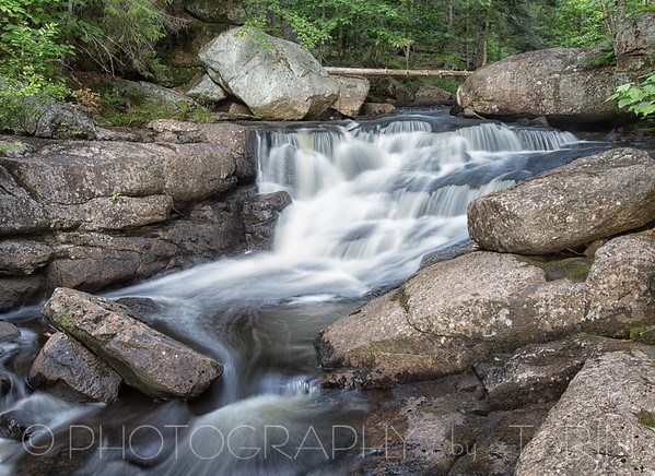 Whiskey Brook Falls. GPS Coordinates: ( 43.52668, -74.38611 ) This very small and easily assessable gem sits right along the eastern (right) side of the road. The falls is 5-6 feet tall and is surrounded by large boulders.