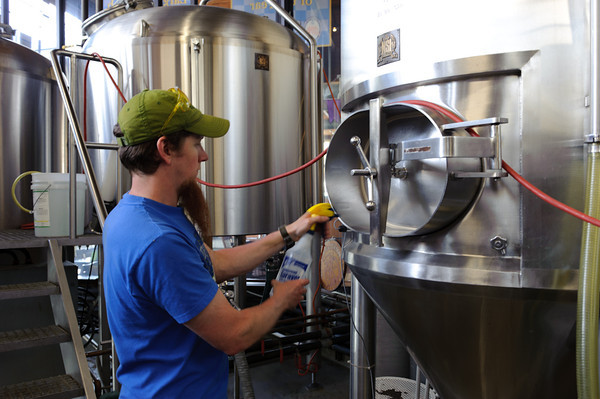Kevin sprays the fermenter door thoroughly with sanitizer getting ready to pitch the yeast.