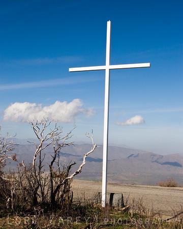 White cross against blue sky in the California desert.