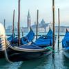 Moored gondolas with San Giorgio Maggiore on the background, Riva degli Schiavoni, Venice, Italy.
