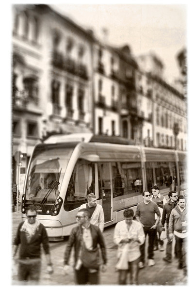 Pedestrians and streetcar on Constitution Avenue, Seville, Spain. Taken with tilted lens to get shallower depth of field and digitally edited to look like an old print.