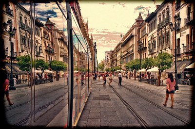 Constitution Avenue reflected on a streetcar, Seville, Spain. Taken with tilted lens to get shallower depth of field and digitally edited to look like an old print.