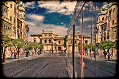 Constitution Avenue (with the City Hall on the background) reflected on a streetcar, Seville, Spain. Taken with tilted lens to get shallower depth of field and digitally edited to look like an old print.