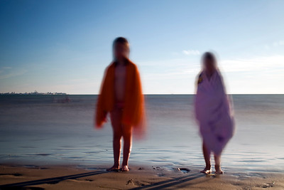 Little girls standing on the beach, El Puerto de Santa Maria, Spain. Daylight long exposure shot by the use of neutral density filters.