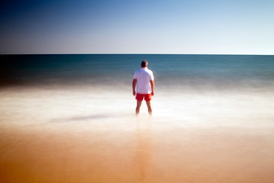 Man on a beach staring at the sea. Daylight long exposure shot by the use of neutral density filters. Model release available.