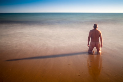 Nude man kneeling on a beach and staring at the sea. Daylight long exposure shot by the use of neutral density filters. Model release available.