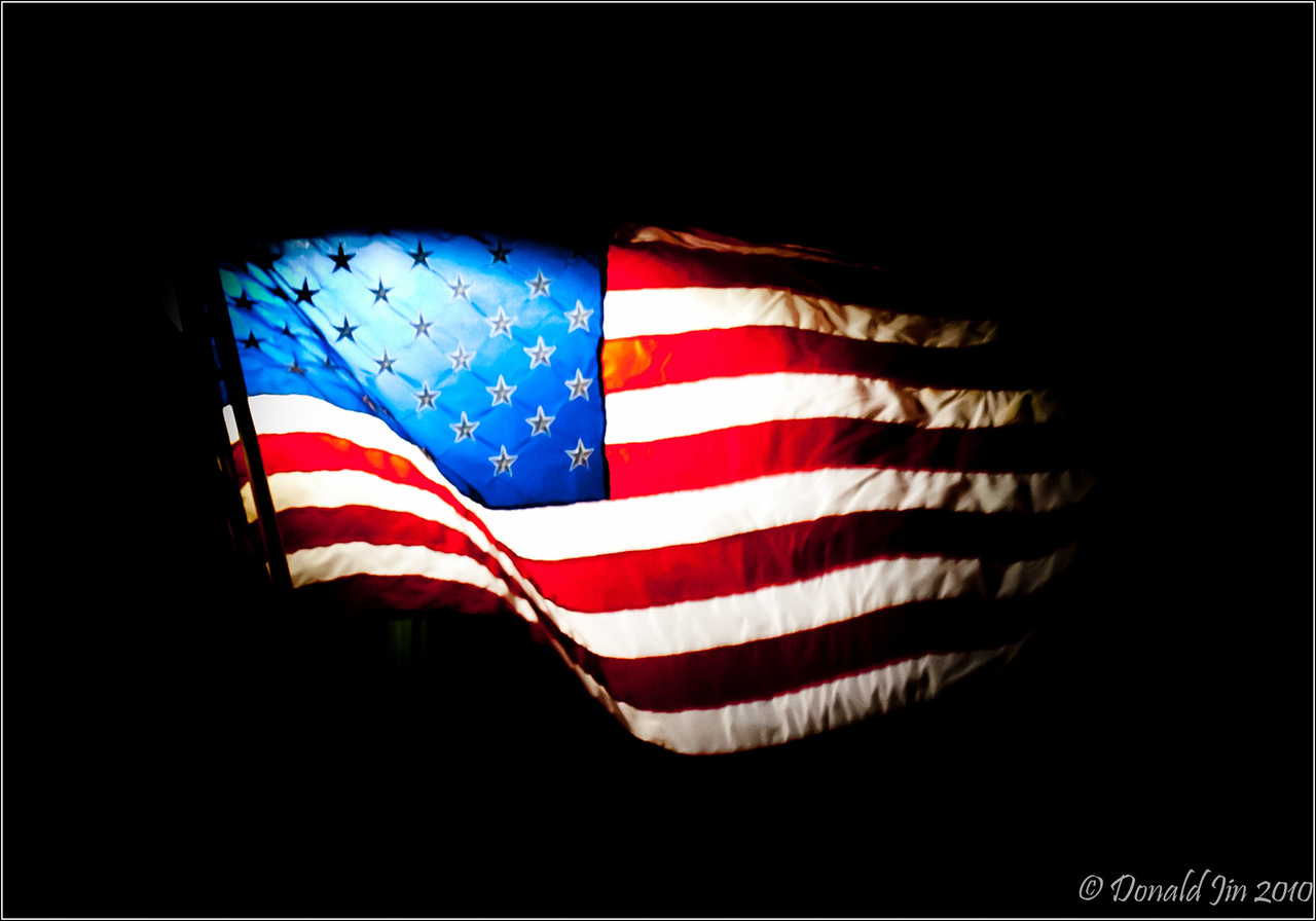 Day 97: Banner That Waved<br /> The town of Sharon had decorated their street lamps on Main Street with brand new American flags.  I was driving home late tonight and this flag fluttering in the night sky back lit by the light from a lamp post caught my eyes.