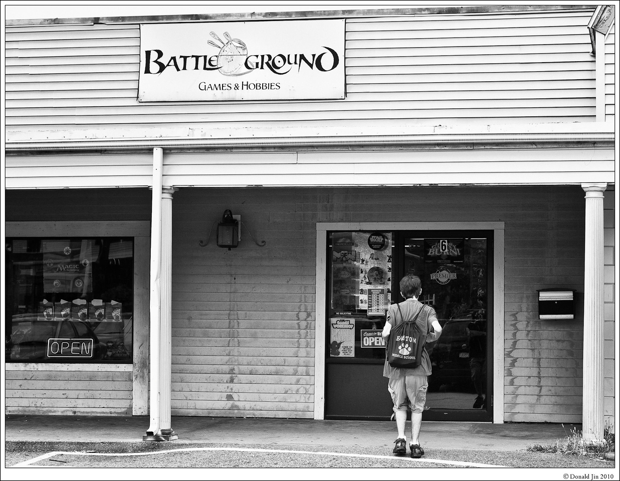 Day 53: There Can Only Be One<br /> Behind this unassuming storefront in a small New England suburban town, a battle of epic scale is planned for tonight.  Wizards are laying out their land to fuel their mana, lining up deadly creatures to summon and planning their most powerful spells to ultimately bring down their opponents.  At the end of the night, only one wizard will remain standing.  This is the place where magic happens – that's Magic: The Gathering.  Today, after Sunday service, Alex had only one thing on his mind - the MTG tournament.  He was rushed over to this little store where grown men and teenage boys alike gathered to show off their collection of Magic card decks and battle it out for the ultimate bragging right.