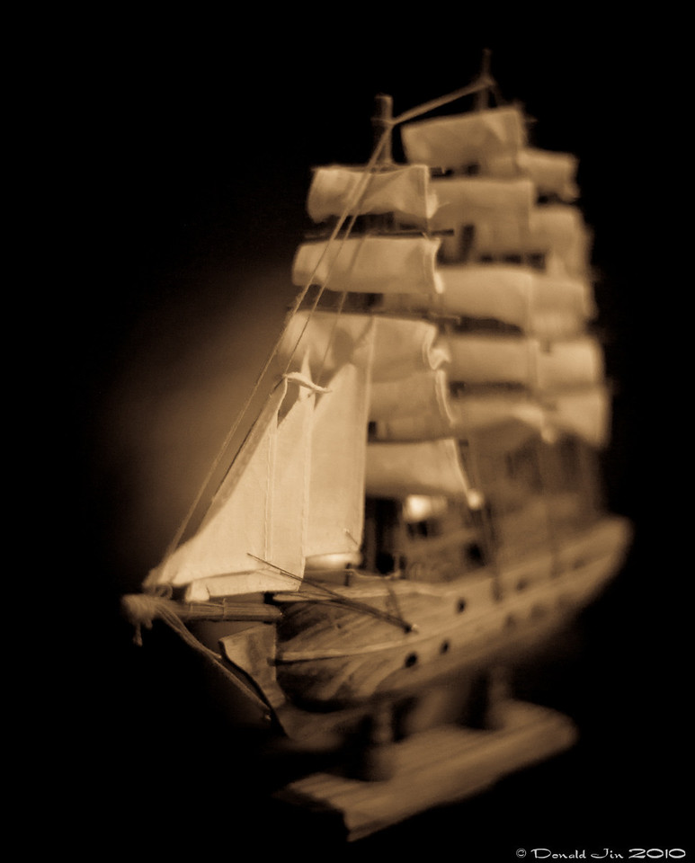 Day 105: Fun with 50mm<br /> This model sailing ship sits atop Alex's bookcase in his room.  I thought I could do something creative with my 50mm set at f/1.4 and some creative lighting.  The final image came out ok but sort of blend.  I think I could have been more original with the camera angle or even the play with depth of field.