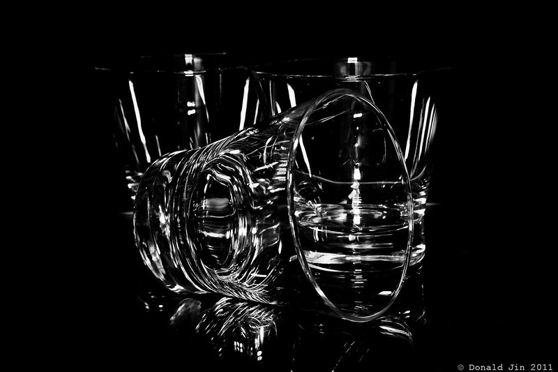 Day 286: Glasses on Black<br /> This photograph was inspired by an image I saw in a magazine today, except the image I saw was a photo of colored glasses stacked on top of each other.  Rather than colored glasses, I wanted to capture a set of perfectly clear glasses in a completely black background.  The trick was to control the harsh glare from the flash by using a snoot on the flash and gobos, a set of black boards that absorbs light, thereby enabling you to control exactly where and how much glare appears on the subject.