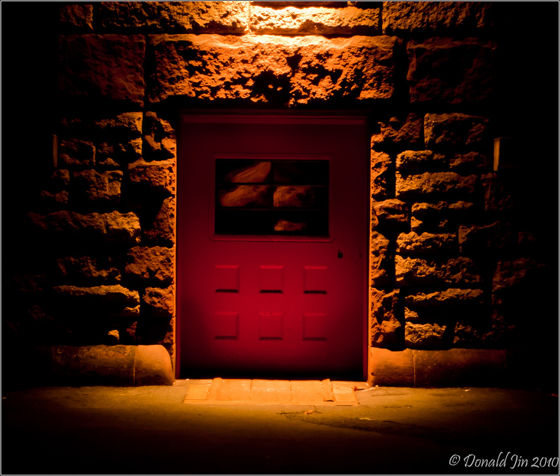 Day 82: Behind The Red Door<br /> I made this photo at an abandoned train station in Easton tonight.  It was almost pitch black except for one lamp shining over this red door.  I thought the lighting, the deep red color of the door and the shadows on the stone wall made for an interesting image.  After couple of shots, I noticed the reflection in the window but couldn't figure out where it was coming from.  There were no other lights except for the one over the door.  The sky was completely black with no moon or stars.  What was really strange was that the reflection was shimmering as if it was floating on water.  I guess if this was a scene from a horror movie, I would get a flashlight from my car and go investigate.  Sorry to disappoint but this is real life.  I quickly packed up my gear, got in my car and peeled out of that parking lot.  For the record, I wasn't scared; I was late picking up my daughter at the Y.  <br /> <br /> Looking at the image on my computer now, doesn't it look like someone's face is looking out the window?