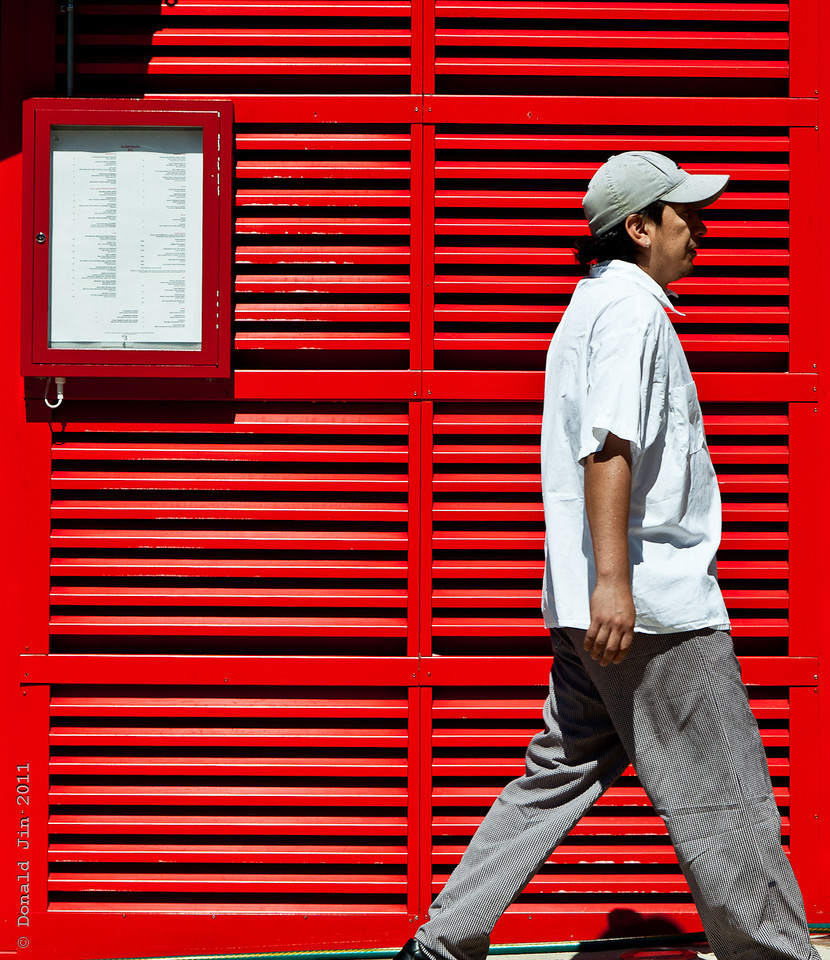 Day 330:  Walking Color Palette<br /> Driving through SOHO today, this bright red paneling in front of a restaurant caught my eyes.  I found a parking spot, illegal but close by and I prepared my camera.   I waited for the right subject, in this case, a splash of complimentary color to pass by to complete the picture.  This was a busy street so I had many subjects walk by but the tricky part was getting a single person with the right color combination and the right gesture.  After many outtakes, I caught this magic moment.