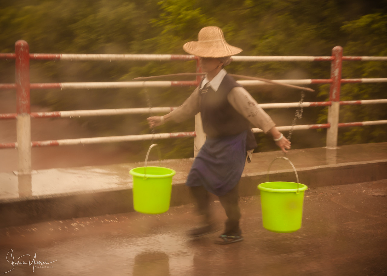 Chinese Woman carrying buckets of water in the rain, outside Dali, China