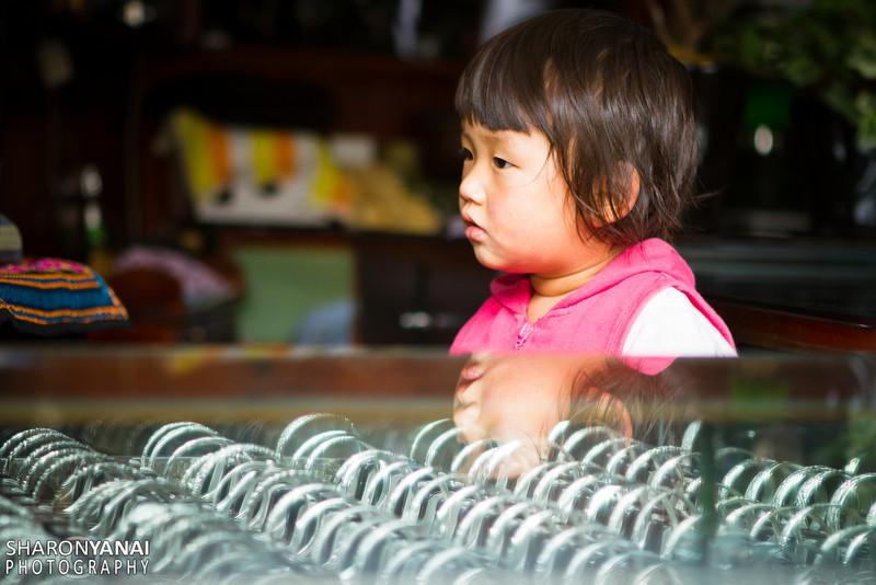 ילדה בוהה בטלויזיה בחנות התכשיטים המשפחתית, ליג'יאן, סין