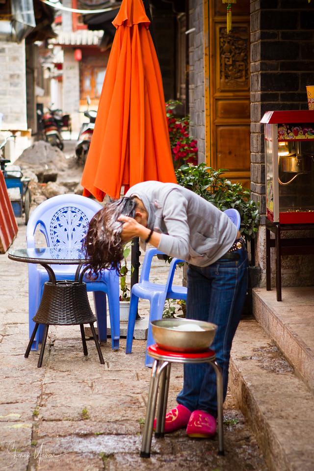 חופפת ראש בבוקר בחזית החנות בליג'יאן, סין