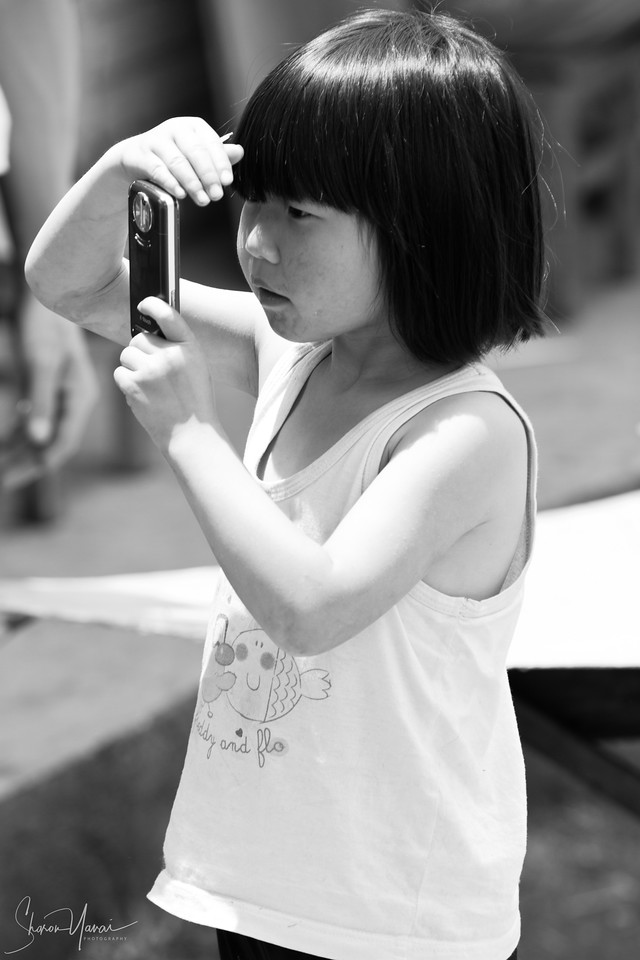 ילדה מצלמת את אמא בשוק בלונגפאנסיאנג, סין