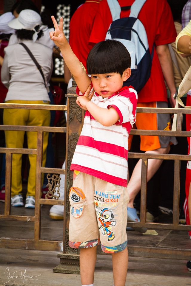Kid making V sign at the Imperial City, Beijing, China