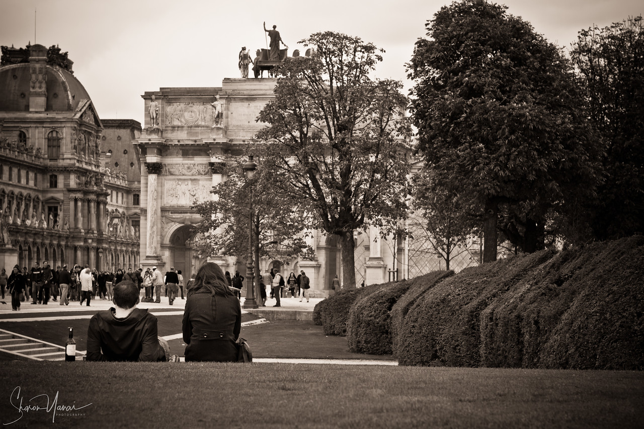 Couple picnic in front of the small Arc de Triomphe, Paris, France