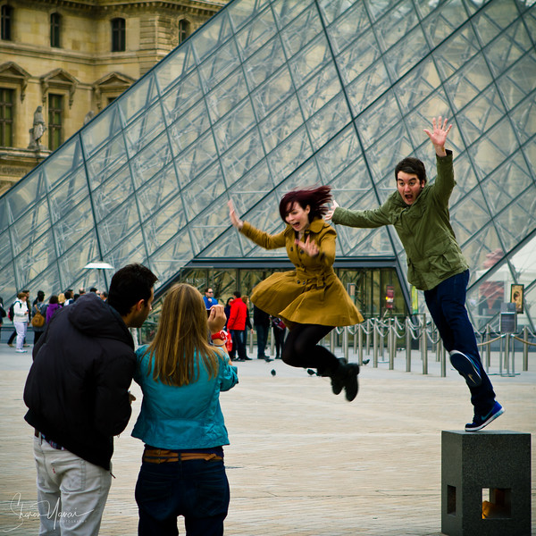 Jumping and taking photos at the entrance to the Louvre, Paris, France