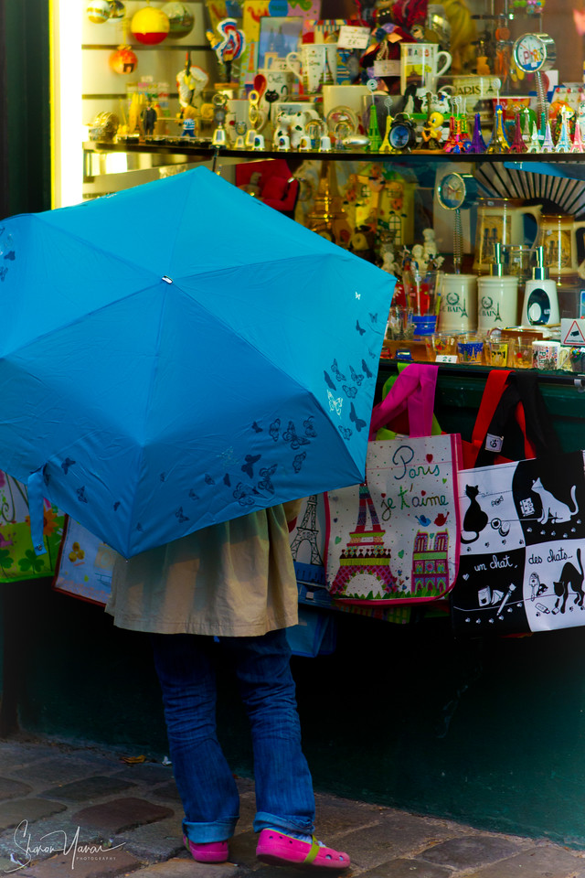 Girl with an umbrella watching the shop window at the Montmartre, Paris, France