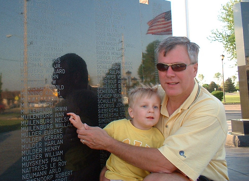 "Grandson of Ivan Muilenburg pointing to his Grandfather's name on a WWII memorial in Orange City, Iowa.  Cpl Ivan Muilenburg proudly served in WWII  87th Infantry Division 549th AAA AW BN BTRY C Battle Of The Bulge   Please make contact if you are connected in any way to any of the names shown in the gallery of names under the  549th AAA AW BN BTRY C group picture!   Photo contributed by Tim Muilenburg.  Book suggestions to read:  #1   ""Battle, the Story of the Bulge,""              Author  - John Toland.   # 2  ""The Bitter Woods:        The Battle of the Bulge,""        Author - John S.D. Eisenhower.      (He's the son of General Eisenhower)   #3.  ""A Time for Trumpets,""           Author -  Charles B. MacDonald.       MacDonald commanded a rifle company in      the Battle of the Bulge."