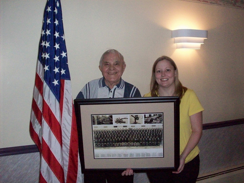 1st Sgt Oliver Santangelo and his grandaughter, Katie<br /> Memorial Day - 2009. <br /> <br /> He served in the 549th AAA AW BN - Btry C.<br /> <br /> <br /> Update May – 2009<br /> Another contact from this unit!!<br /> 1st Sgt Oliver Santangelo<br /> drafted on 12/01/1941 in Canton Ohio.<br /> <br /> An email from his stepson, Charlie Craig:<br /> My daughter and I had a recent conversation with my step dad. <br /> He showed us his Army discharge papers and we wrote down his unit number. <br /> To our surprise we found his pic on that 87th site. <br /> He is Oliver Santangelo. <br /> He is 1st. row 7th from the left. <br /> We bought the picture and are having it framed and giving it to him on Memorial day to honor him and the men he served with. <br /> He is 89 and still sharp as a tack. <br /> Thanks,<br /> Charlie<br /> <br /> I replied asking him to send more info which I will place here once I receive it.<br /> I also cropped his photo from the large unit photo and have placed it in the gallery.<br /> Isn't this amazing!<br /> <br /> Update - June 1 - 2009<br /> Email from Mr. Santangelo's stepson, Charles Craig:<br /> <br /> On Memorial Day, we gave Ollie (Mr. Oliver Santangelo) the framed photo <br /> of the 549th AAA unit – Btry C. <br /> He was shocked and really touched that we were able to find it. <br /> <br /> I did ask him about the names you gave – <br /> He remembers Mr. Luedke.<br /> He said that during training at Camp Davis, <br /> he and Mr. Luedke had to escort the body of a young man back home. <br /> The soldier had accidentally killed himself while cleaning his rifle.<br /> <br /> He could not recall where they were for the early part of December of 44,<br /> But claims that the 549Th was in Bastogne during the Battle of the Bulge. <br /> Ollie says that they couldn't get air cover for 4 days due to the weather.<br /> <br /> Ollie and my Mom attended a reunion in St. Louis/Bran son, but he couldn't recall what year.<br /> I will ask him abo