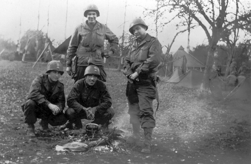 "November 1944 in Critot, France.<br />  <br /> Shown L to R:<br /> <br />     * PFC Hershell H. Teeples (Later transferred to B Company)<br />     * PFC Kenneth J. Born (Later transferred to A Company)<br />     * PFC John H. ""Dip"" Evans (Later transferred to C Company - KIA Rhens, Germany, 28 March 1945)<br /> <br /> Standing in back:<br /> <br />     * PFC Earle J. ""Joe"" Hewitt (Later transferred to A Company, and later yet Hqtrs Co, 347th)<br /> <br /> An interesting shot of a group of AT gunners not long after arrival in France. The guys are shown wearing helmet liners with what looks like divisional and rank insignia. They are wearing the old style leggings wool trousers and field jackets. Joe Hewitt is shown wearing a .45 pistol on his web belt. As I remember him telling me he traded this for an M1 rifle at his first opportunity once they got into combat!"