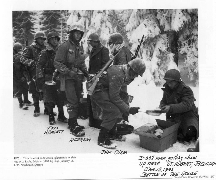 """I-Company, 347th Infantry.; 87th Infantry Division<br /> January 13, 1945<br /> Battle of the Bulge<br /> <br /> This is letter sent to Army HQ by John McAuliffe<br /> describing photo and giving information about it:<br /> <br /> Dear Sirs:<br /> For your information I have enclosed the famous and popular photo found in most Army History books related to the<br /> """"Battle of the Bulge""""....<br /> <br /> Unfortunately most books do not give credit to the photo and identify it. <br /> <br /> The photo is of I-Company, 347th Inf.; 87th Infantry Division. <br /> It is an Army Signal Corps photo with the caption,<br /> """"On the road to La Roche"""".....<br /> <br /> Unfortunately the unit did not go to La Roche but went into action in January 1945 at Moircy,Tillet, Bonnerue in Belgium. <br /> <br /> The unit arrives here to get the new issue of galoshes as seen in the photo. <br /> <br /> The soldier with carbine over shoulder receiving his portion is John Olson of Arlington Heights, ILL and still lives there.<br /> <br /> Other soldiers are identified. Tom Hewlet with the forlorn eyes died early after the war, but his son Tom Hewlett and wife Pat attend the 87th Div. Assoc. Reunions as does Olson and his wife.<br /> <br /> The Company Commander of I-Company, 347 Inf. was and still is Captain Ray E.Miles, who lives in Richmond, VA.<br /> <br /> I am sending you this information for your observation and possiblity for your Headquarters to properly identify this photo for posterity.<br /> <br /> My qualifications are that I am a former member of M-347; <br /> 87th Inf. Div WW-II. I am the Past Commander of the 87th Inf. Div. Association; I am  current Vice Pres. of Chapters for the National Veterans of the Battle of the Bulge Inc; I am  current Pres. of the Cent. Mass. Chapt.-22;VBOB....<br /> <br /> This photo tells a lot; Just look at it ; examine it  and from the clothing and the surrounding snow draped fir trees, one may get an inkling of what it was like in the ARDENNES C"""