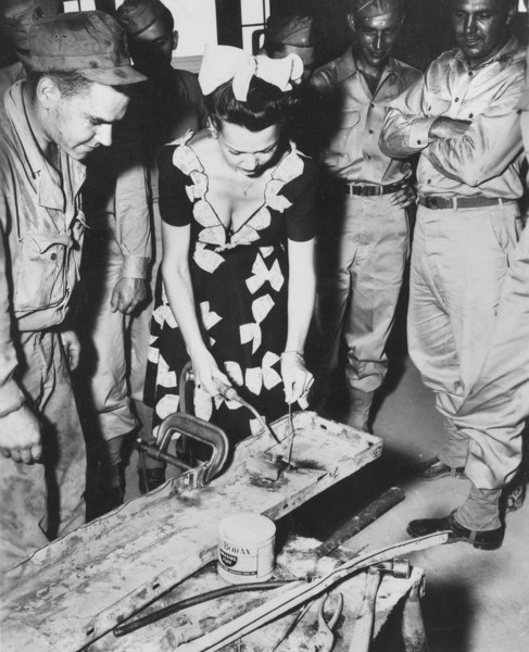 Actress Carol Landis tries her hand at welding in one of the 87th Division repair shops.