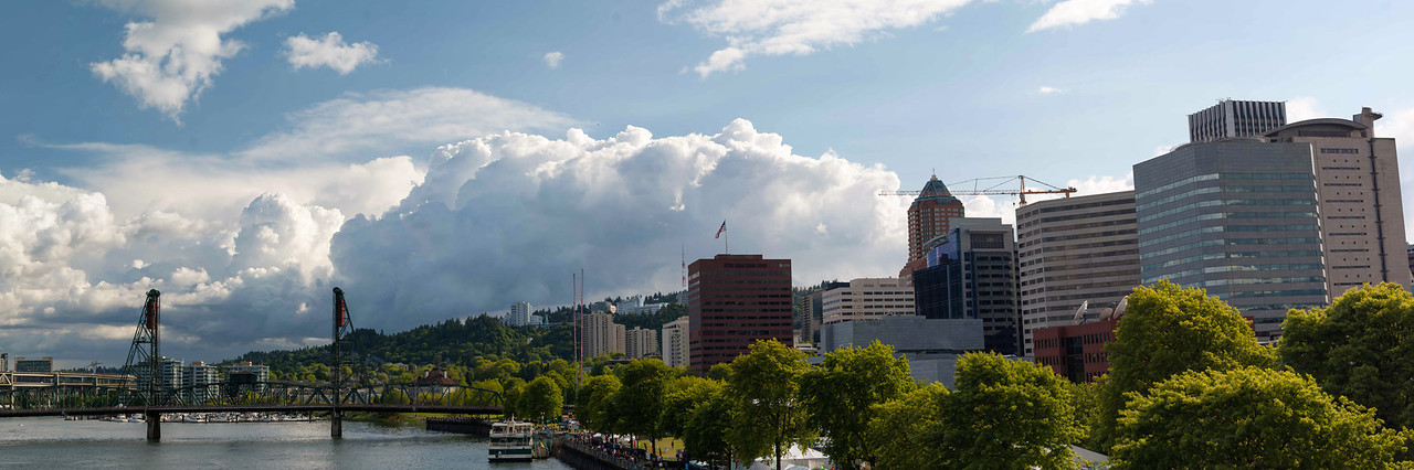 "Portland Stormfront <br /> A photo of downtown Portland during the Rose Festival. Storm clouds are rolling in over the hills. <br /> Purchase this photo at the top right by clicking ""buy"".<br /> 1x3 printing format<br /> 30""x90"" Max printing size<br /> Displayed at 12""x36"""