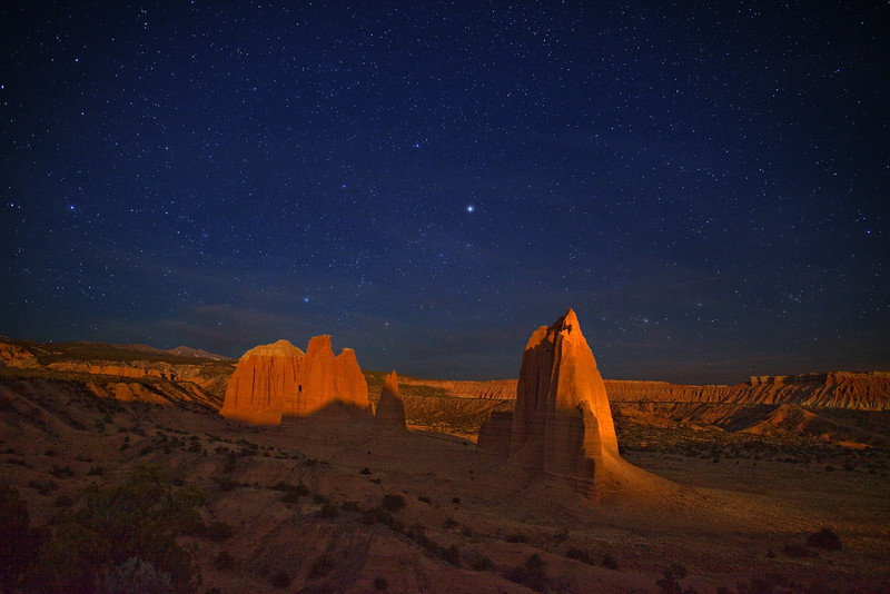 Moonlight across Cathedral Valley. Starry night sky with moonlight streaking across the Upper Cathedral Valley monoliths in Capitol Reef National Park, Utah. This is a remote area in the northern most region of the park that is only accessible with a four-wheel drive vehicle via primitive dirt roads and river crossings! The monument on the right is about 400 feet (122 m.) high. It is enhanced with light painting from two stationary incandescent lights and one handheld, 2-million candlepower quartz halogen light -- from a distance of 900 feet (274 m.) away.
