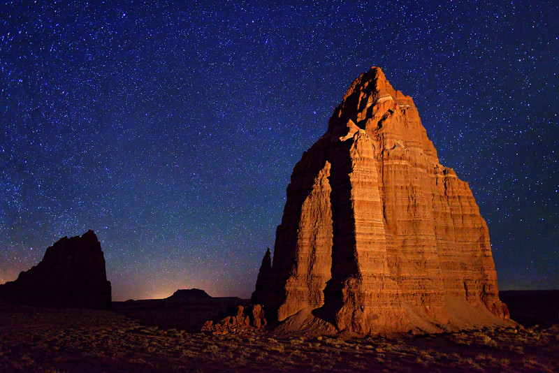 Starry night sky over Temple of the Moon - a sandstone monolith located in the remote Cathedral Valley of Capital Reef National Park. Temple of the Sun is in the distance, on the left. The Temple of the Moon is about 280 feet (85 m.) high. Photographed in one 15 seconds exposure, 2 hours after sunset. The glow on the horizon is the approaching moonrise.