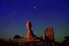 Starry Night sky over Balance Rock in Arches National Park. As tall as 23 men, or a 13-story building --the total height of Balanced Rock is about 128 feet (39 m), with the balancing rock rising 55 feet (16.75 m) above the base. The big rock on top is the size of three school buses. This sandstone formation has been light painted from a distance of about 450 feet by a moving, diffused, quartz halogen light (from camera left). Camera direction is northeast. Photographed about three hours after sunset.