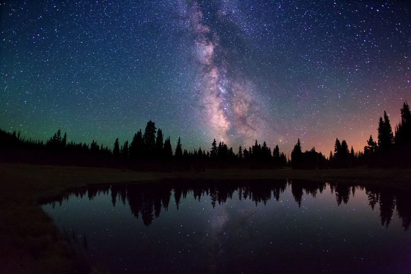 Milky Way stars over an unnamed lake near Hayden Pass (10,375 ft. / 3,162 m.), on the edge of the High Unitas Wilderness, Utah, USA. Red glow from Salt Lake City metro area, 55 miles (89 km) away.