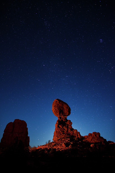 Moon glow from the rising quarter moon, directly behind Balanced Rock, Arches National Park. The midnight moonlight from the rising moon is overpowering all but the brighter stars. However, you can clearly see Pleiades, the Seven Sisters constellation (Messier object 45 or M45) to the right. Light painting for Balanced Rock is coming from a stationary, reflected quartz halogen spotlight (2-million candlepower) about 300 feet away.