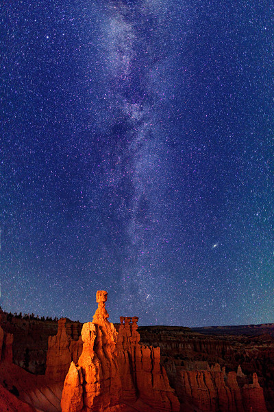 Starry night sky and the Milky Way over a light-painted Thor's Hammer, in Bryce Canyon National Park