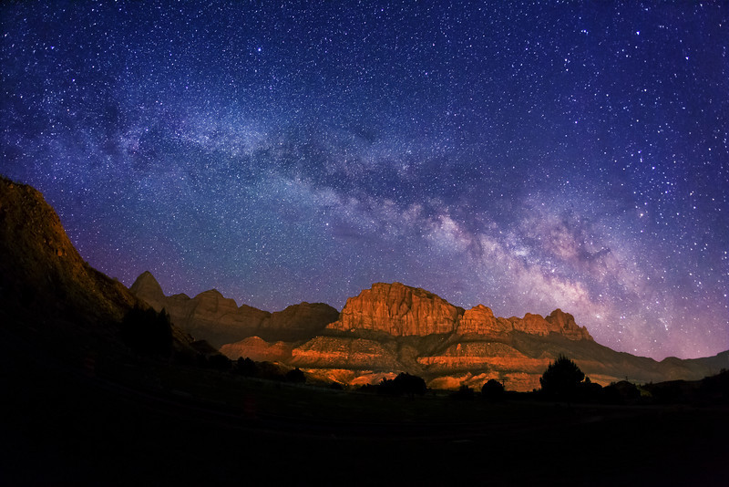 """Milky Way stars over Zion National Park. Springdale, Utah is the entrance to Zion National Park, and is surrounded on both sides by the the park. The mountains are illuminated by the reflected lights from this small town. The mountain in the center is called """"The Watchman""""."""