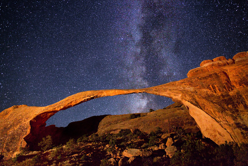 Milky Way stars over a light-painted Landscape Arch, in Arches National Park.