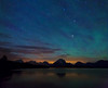Airglow and faint aurora borealis or northern lights (due to recent massive solar flares</a>) seen over the Teton Range on July 17, 2012 at 12:55 AM, as clouds roll in. Twenty minutes later, the sky was almost completely obscured with cloud cover. This is looking over Jackson Lake. The light on the lake is from the Signal Mountain marina. The Grand Teton is on the far left. Mount Moran is in the center (directly west @ 270º). Above Moran is the yellow-orange star, Arcturus, and the bright one above that is Izar, both in the constellation Bootes (see notes). The brightest blue star at the very top (directly in line with Moran) is Alphekka, in the constellation Corona Borealis.