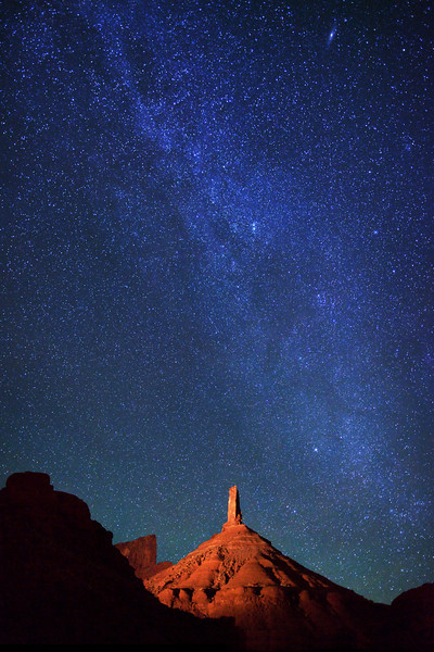 Starry night sky and the northern tail of the Milky Way over the light-painted Castle Rock, a sandstone monument in Castle Valley, Utah. The top portion is called Castleton Tower.