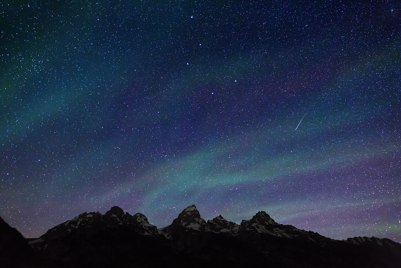 Starry night sky over Teton Range, Grand Teton National Park. Cirrus clouds, backlighted by stars give the impression of an aurora borealis. Note the meteor and a portion of the Big Dipper pointing to the North Star, Polaris, in the top right corner.