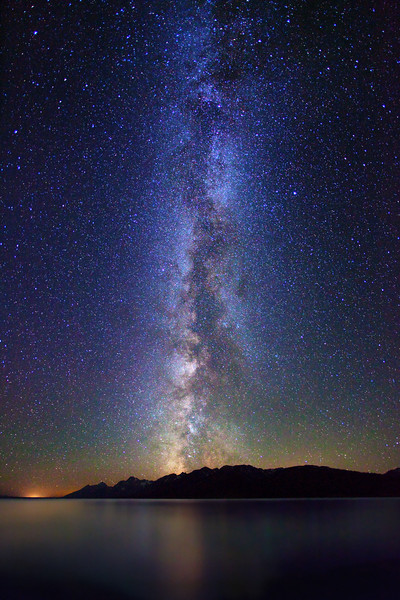 Milky Way stars over Teton Range and Jackson Lake, Grand Teton National Park. Glow on left horizon is light pollution from the town of Jackson, Wyoming, about 30 miles away.