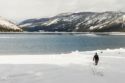 Man walking dog by lake in snowy mountains