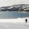 Man walking dog by lake in snowy mountains