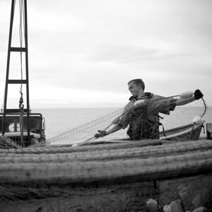 Jefferson Klapak, 18, hangs a net out after a day of fishing on the Johnson's beach site.