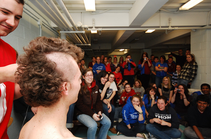 Collegian Photo By: Jimmy Dever Joe England shaves Greg Plumb's head as fellow students look on and support them Thursday night.