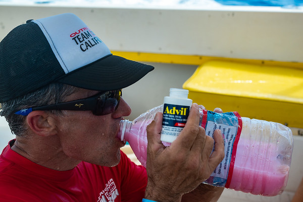 After four hours, the toll of the constant confused water, sun, swimming, water changes and of course paddling is apparent. Scott Granger downing some pain killers with his drink of choice to get him through the last stretch of the race.