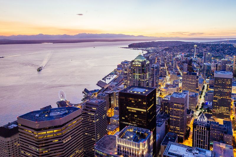Aerial view of downtown Seattle with Space Needle, Washington State ferry and Pugest Sound at sunset