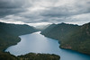 Aerial view of a large mountain lake surrounded my mountains with a cloudy sky