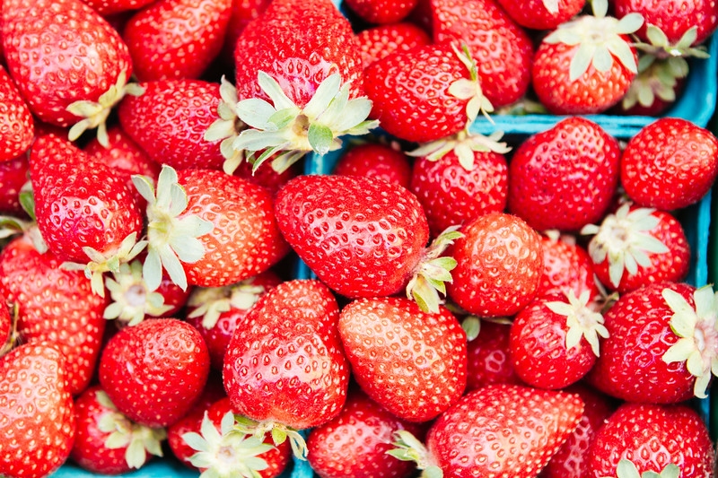 Bird's eye view of fresh, local, organic strawberries in individual containers at an outdoors farmers market